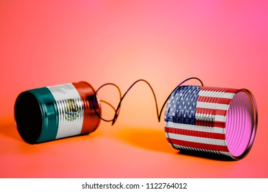 tin can phone with USA and Mexico Flags.communication concept on pink