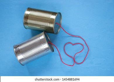 Tin can telephone on a blue background