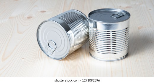 Tin cans for food on white wooden table