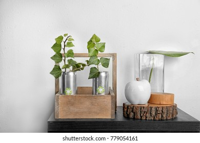 Tin cans with plants on table near light wall. Waste recycling concept
