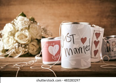 Tin cans for a wedding car with hand drawn sketches depicting red hearts and text - Just Married - on a wooden table with bridal bouquet of white roses