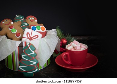 Tin of Christmas Gingerbread with Hot chocolate and Marshmallows on Dark Background with Copy Space