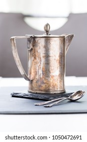 A tin coffee percolator and two metal spoons