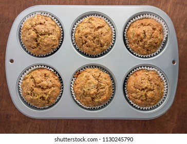 A tin of freshly baked zucchini banana muffins on wooden table.