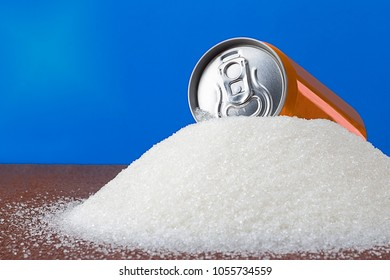 Tin orange can with a cool drink on top of a heap of sugar on a blue background. Diabetes, sugar free and harm concept.