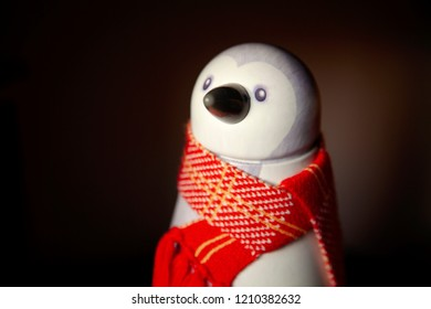 Tin penguin, with red scarf, against a dark background