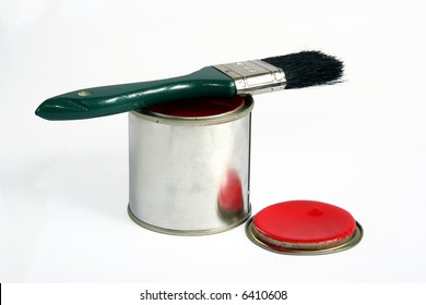 Tin of red paint with a brush on top of it