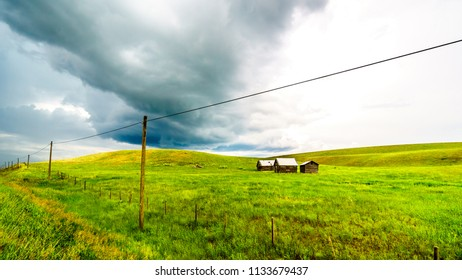 Tin Roofed Barns in the wide open Grass Lands of the Nicola Valley, along Highway 5A between Merritt and Kamloops, British Columbia, Canada, under dark threatening sky