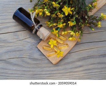 Tincture in a bottle, oil in capsules and saint johns wort herb on a wooden table, flat layout. Medicinal plant hypericum perforatum for use in herbal medicine, homeopathy and cosmetology