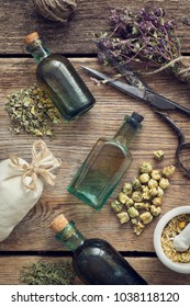 Tincture bottles, assortment of dry healthy herbs, mortar, sachet, scissors. Herbal medicine. Top view, flat lay.