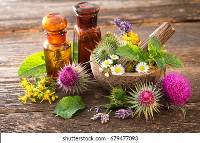 Tincture bottles and healing herbs in mortar on wooden table