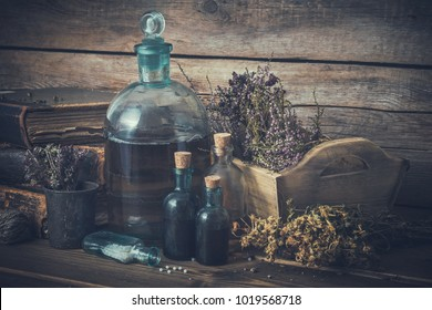 Tincture bottles, vial of homeopathy globules, old books, assortment of dry healthy herbs and curative drugs. Herbal and homeopathic medicine. Retro styled.