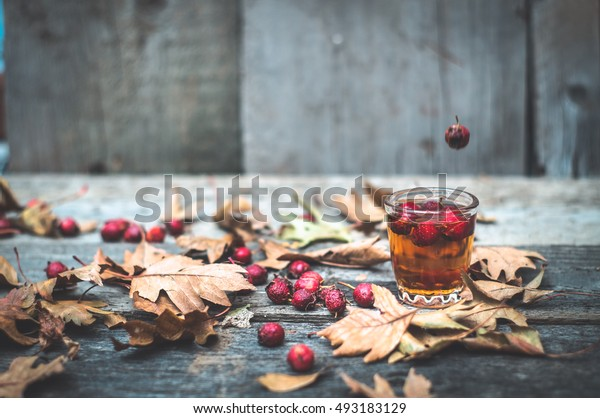 tincture of hawthorn in a glass transparent with autumn leaves on the wooden table