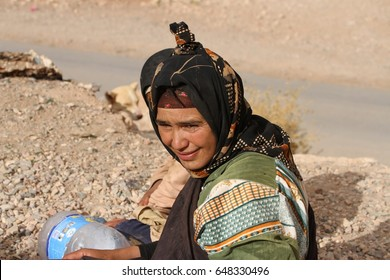 TINERHIR, MOROCCO - AUGUST 20: A closeup of a Berber woman in traditional dress sitting on a clifftop at Todgha Gorge, Tinerhir, Morocco on the 20th August, 2015.