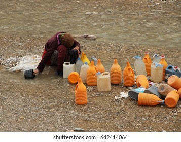 TINERHIR, MOROCCO - AUGUST 20:  A nomad female in traditional dress collecting fresh water from the river at Todra Gorge, Tinerhir, Morocco on the 20th August, 2015.