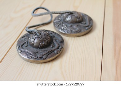 Tingsha (Ting-sha), Tibetan meditation bells in close up, isolated on a natural wooden background. Selective focus, copyspace to right.