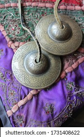 Tingsha (Ting-sha), Tibetan meditation bells in close up, laying on a colorful indian cushion. Selective focus, copyspace underneath.