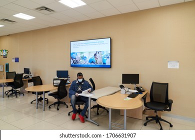 Tinley Park, IL, US – April 16th 2020: CarMax Empty Showroom; One isolated customer wearing PPE mask in the showroom reviewing and signing documents to finalize a car purchase.