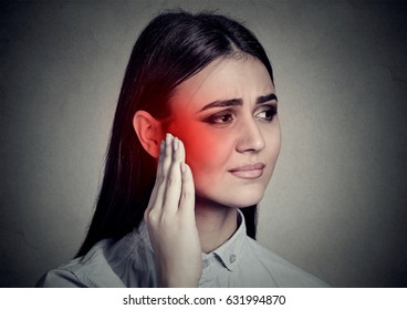 Tinnitus. Closeup sick woman having ear pain touching her temple head isolated on gray wall background