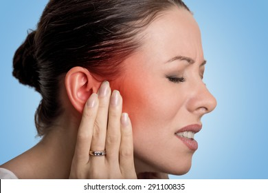 Tinnitus. Closeup up side profile sick female having ear pain touching her painful head isolated on blue background