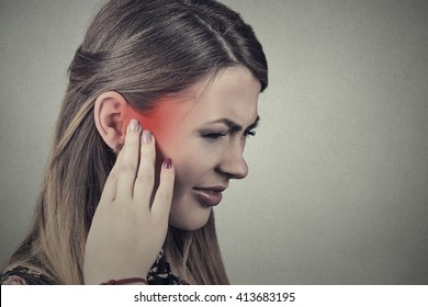 Tinnitus. Closeup side profile sick young woman having ear pain touching her painful head temple colored in red isolated on gray background