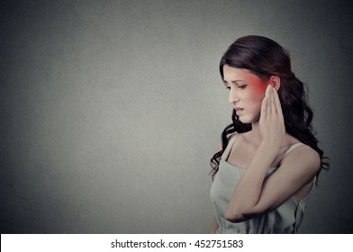 Tinnitus. Closeup up side profile sick female having ear pain touching her painful head temple colored in red isolated on gray wall background with blank copy space