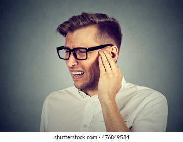 Tinnitus. Closeup side profile sick young man having ear pain touching his painful head isolated on gray background