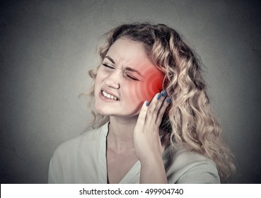 Tinnitus. Closeup up side profile sick female having ear pain touching her painful head isolated on gray background