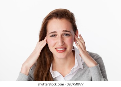 tinnitus concept - sick young woman having painful headache,covering closed ears,annoyed by loud noise not wanting to hear their side of story