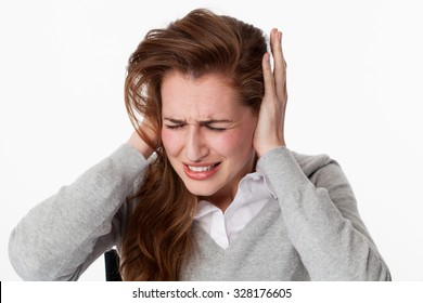 tinnitus concept - stressed out young woman having painful migraine,covering closed ears,annoyed by loud noise not wanting to hear their side of story