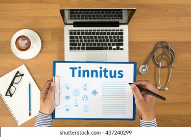 Tinnitus Doctor writing medical records on a clipboard, medical equipment and desktop on background, top view, coffee
