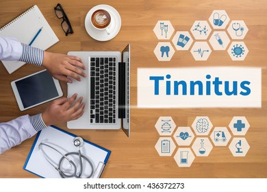 Tinnitus Professional doctor use computer and medical equipment all around, desktop top view, coffee