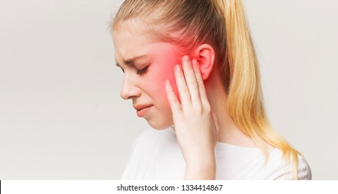 Tinnitus. Profile of sick female having ear pain, touching her painful head, panorama