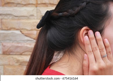 Tinnitus, young woman has pain in the ear