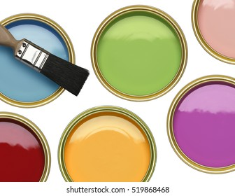 TINS OF BLUE GREEN PINK RED YELLOW AND PURPLE PAINT WITH BRUSH ON WHITE BACKGROUND