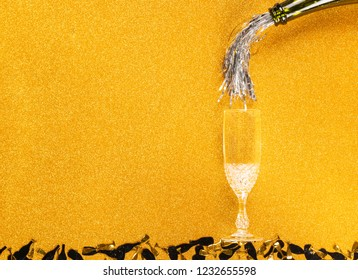 Tinsel pouring from bottle simulating Champagne in two glasses on golden glittering background