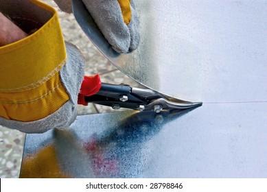 Tinsmith cuts a sheet metal by snips