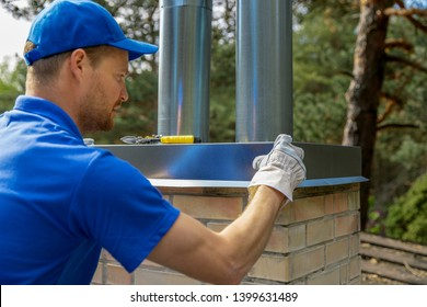 tinsmith on the roof installing tin cap on the brick chimney