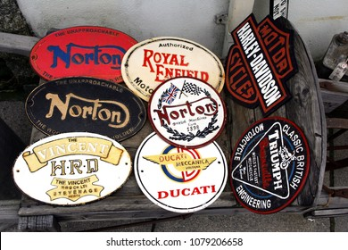 Tintagel, Cornwall, UK - April 10 2018: Enamel plaques or name plates with names of legendary classic motorcycle manufacturers like Norton, Triumph, Vincent, Harley Davidson, Ducatti, Royal Enfield.