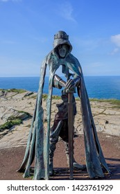 Tintagel, Cornwall, UK - April 10 2018: The King Arthur statue Gallos by Rubin Eynon stands on a rocky headland on the Atlantic coast of Cornwall.