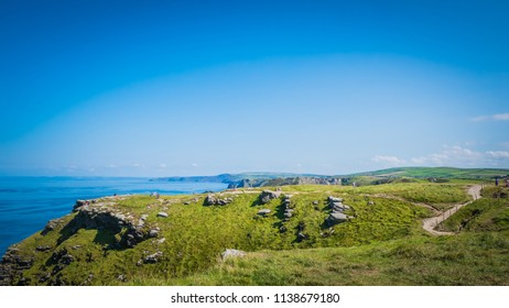 Tintagel island landscape in Cornwall, United Kingdom, UK. Cornish holidays landscape, western UK summer holidays destinations. British cliffs with green grass and rocks by the Atlantic Ocean.