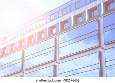 tinted photograph reflection of blue sky with clouds in the glass facade of an office high-rise building