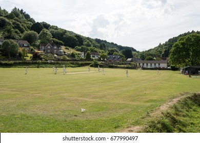 Tintern, Wales, UK.,9th July 2017: Tintern village cricket field and cricket players on a Summer's day in the shadow of Tintern Abbey, with the trees of the Wye Valley in the background.