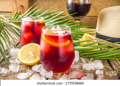 Tinto de Verano or vino de verano, Spanish Wine Cocktail. Refreshment acoholic drink sangria. Cool iced alcohol beverage with lemon juice and slices, wooden background with summer tropical decor - Shutterstock ID 1770538484