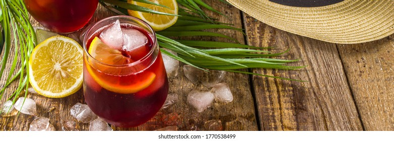 Tinto de Verano or vino de verano, Spanish Wine Cocktail. Refreshment acoholic drink sangria. Cool iced alcohol beverage with lemon juice and slices, wooden background with summer tropical decor - Shutterstock ID 1770538499