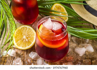 Tinto de Verano or vino de verano, Spanish Wine Cocktail. Refreshment acoholic drink sangria. Cool iced alcohol beverage with lemon juice and slices, wooden background with summer tropical decor - Shutterstock ID 1974767960