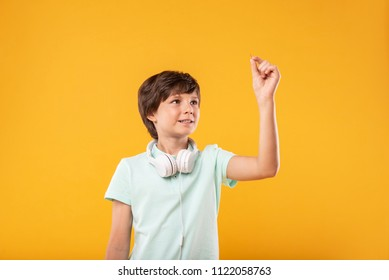 So tiny. Alert smart schoolboy wearing headphones and holding a pin