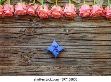 Tiny blue diamond shaped bowed gift box over worn out wooden background with roses on top