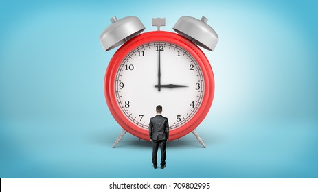 A tiny businessman with his back turned stands in front of a giant red alarm clock. Business vs personal life. Effective work. No time for delay.