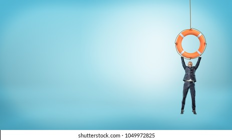 A tiny businessman holds on to a giant orange life buoy with both arms on a blue background.  Business insurance. Help of professional consulting.